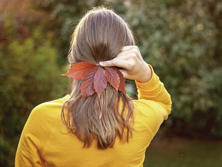 Na imagem uma mulher branca está de costas, ela segura cinco folhas de árvores como se estivessem prendendo seus cabelos loiro escuros. Sua blusa possui mangas longas e é amarela. A paisagem ao fundo está desfocada e é composta por árvores e grama.