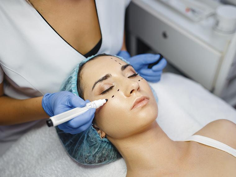 Na imagem uma mulher está deitada em uma maca, seus olhos estão fechados e ela usa uma touca azul no cabelo. Atrás dela, uma mulher de jaleco usa luvas azuis e, com uma caneta marcadora, faz pontos no rosto da paciente.