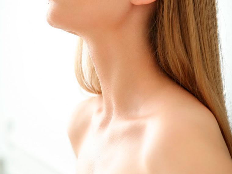 A imagem mostra o perfil de uma mulher branca e loira, com cabelos lisos. É possível visualizar os seus ombros e a área inferior do rosto. Ela está com o queixo voltado para cima. O fundo da imagem é branco.
