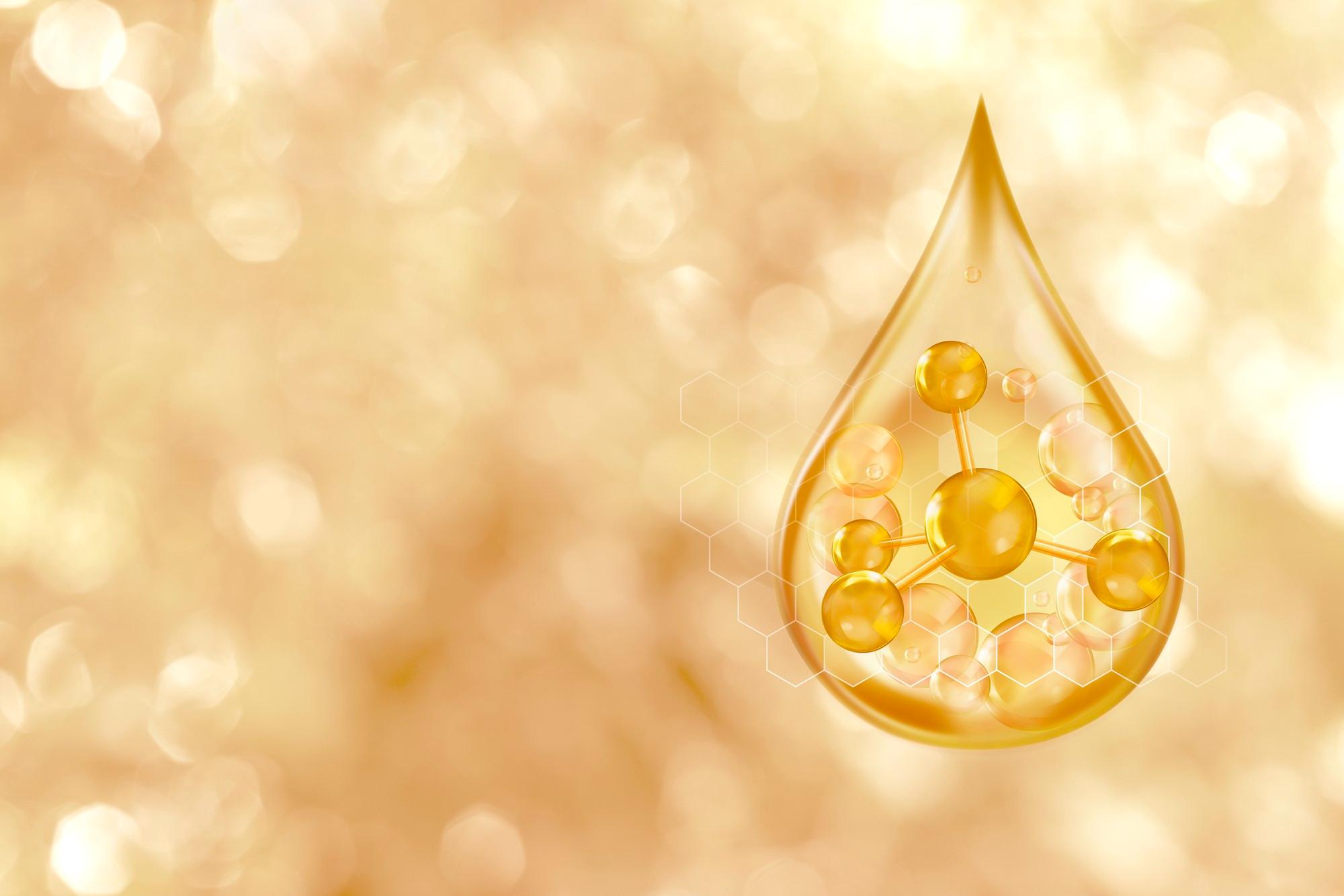 A imagem mostra a ilustração de uma gota dourada, contendo uma cadeia proteica, simulando o colágeno. O fundo é abstrato com cores, predominantemente dourada e branca.